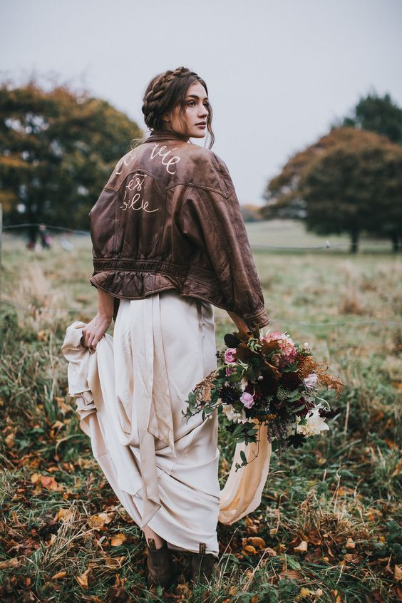 a boho bride wearing a blush wedding dress, brown booties and a brown leather jacket with calligraphy