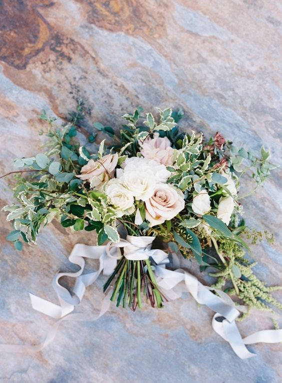 a light-colored wedding bouquet with white and blush blooms and much greenery