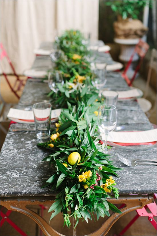 a lush and textural greenery table runner with fruits and yellow flowers incorporated for a bold look