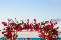 18 a lush beach arch decorated with fuchsia and red blooms lushly and with greenery