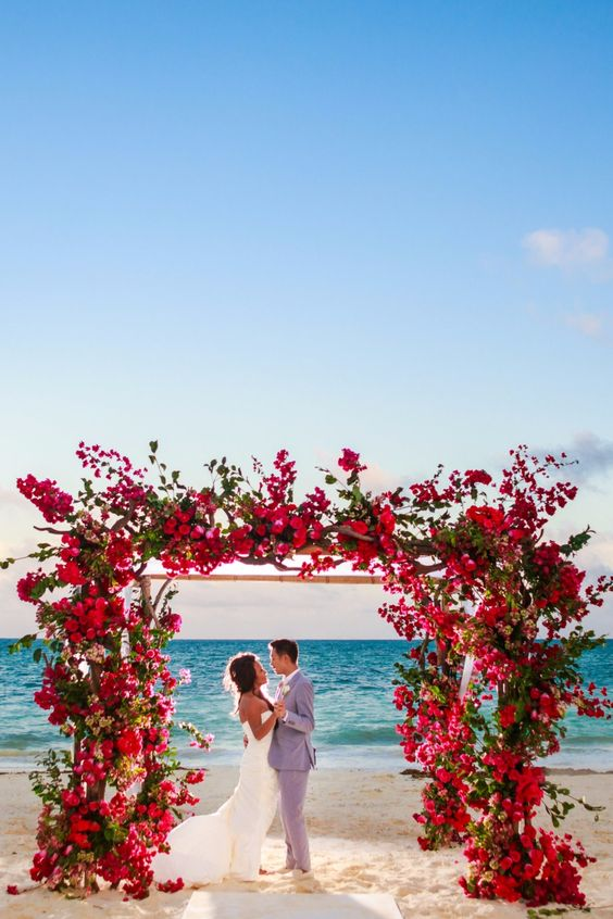 a lush beach arch decorated with fuchsia and red blooms lushly and with greenery