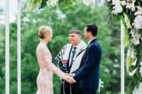 18 a modern tropical wedding chuppah with lush greenery and blush and white blooms hanging down