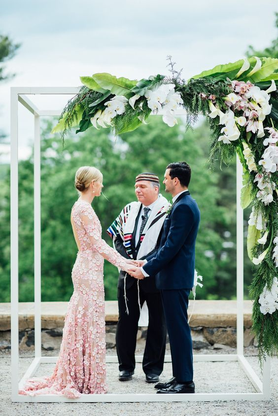 a modern tropical wedding chuppah with lush greenery and blush and white blooms hanging down