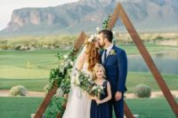 19 a double triangle wedding arch covered with greenery and white blooms plus a rug for a beautiful outdoor look
