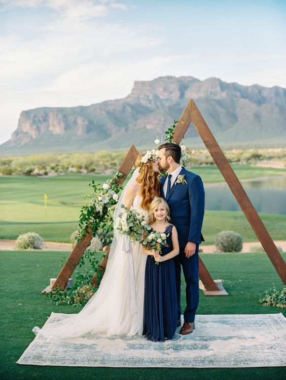 a double triangle wedding arch covered with greenery and white blooms plus a rug for a beautiful outdoor look