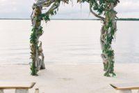 19 a driftwood wedding arch interwined with fresh greenery for a tropical beach wedding