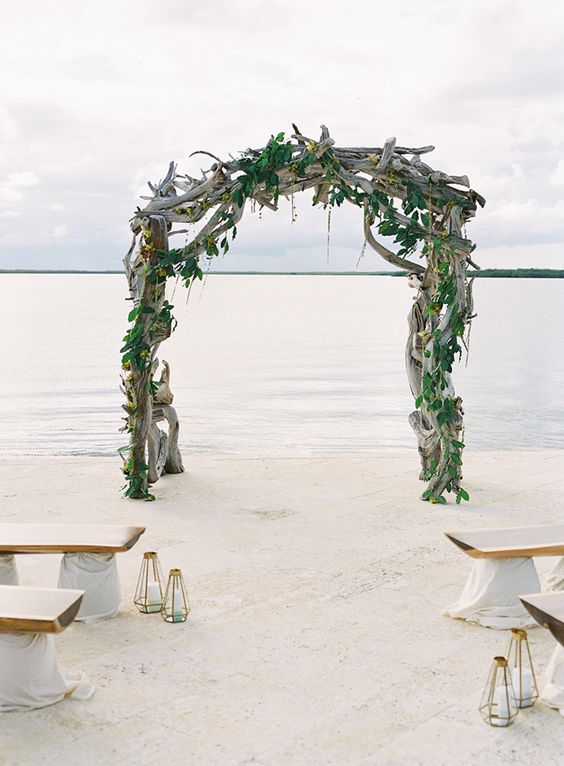 a driftwood wedding arch interwined with fresh greenery for a tropical beach wedding