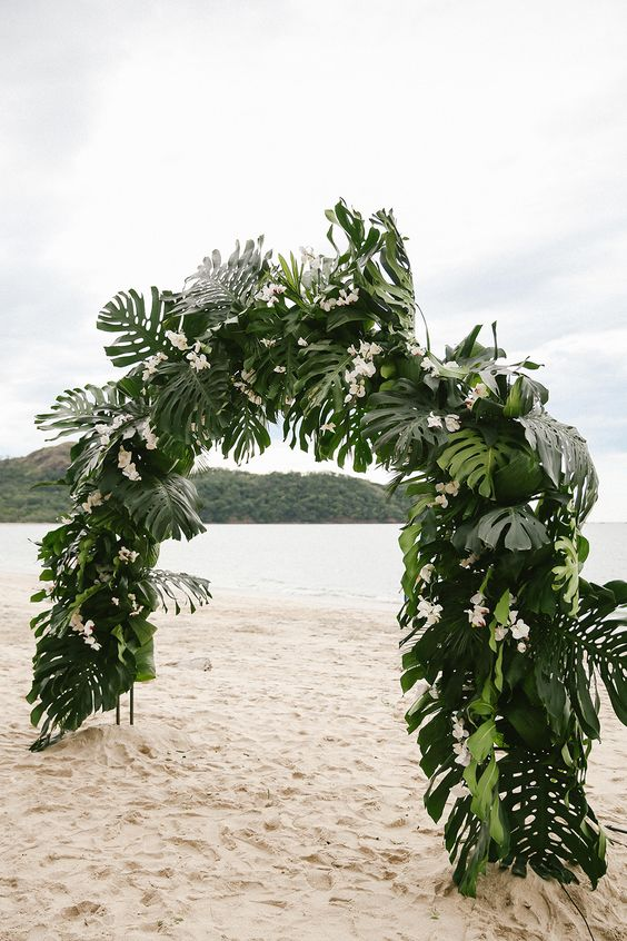 a lush semi circle wedding arch with tropical leaves and white blooms on the beach