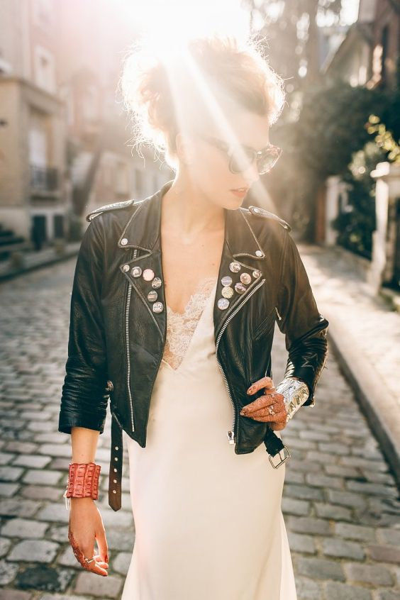 a rock n roll bride in a romantic dress, a black studded jacket and with a cool updo