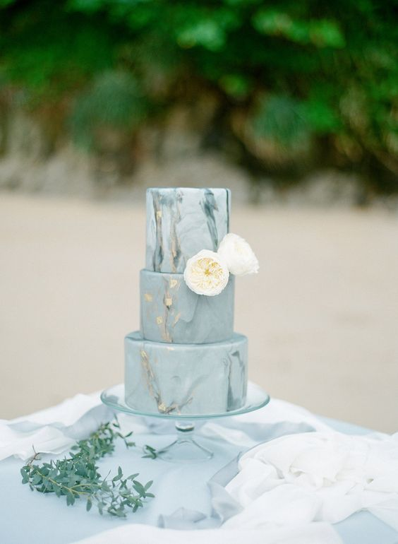 a slate grey wedding cake with a marble effect and gold leaf topped with neutral blooms