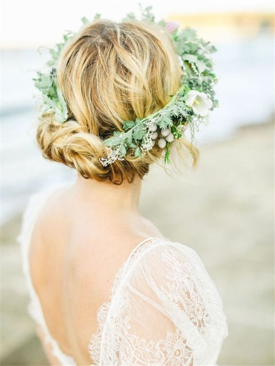 a twisted updo with some locks down and a greenery crown can be worn with medium or long hair