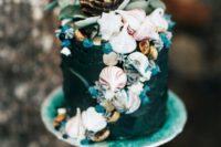 20 a boho mermaid wedding cake in dark teal, with meringues showing shells, greenery and a bloom