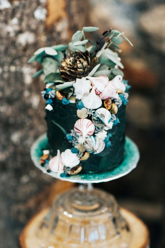 a boho mermaid wedding cake in dark teal, with meringues showing shells, greenery and a bloom