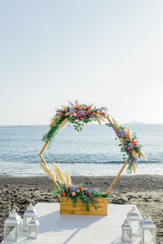 a creative hexagon wedding arch decorated with colorful blooms, greenery and pampas grass