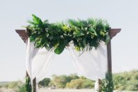 20 a lush tropical wedding arch done with airy white fabric, tropical leaves and white blooms
