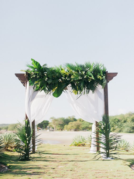 a lush tropical wedding arch done with airy white fabric, tropical leaves and white blooms