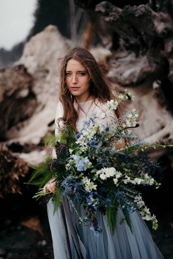 a moody bridal bouquet with white and blue flowers and leaves and greenery