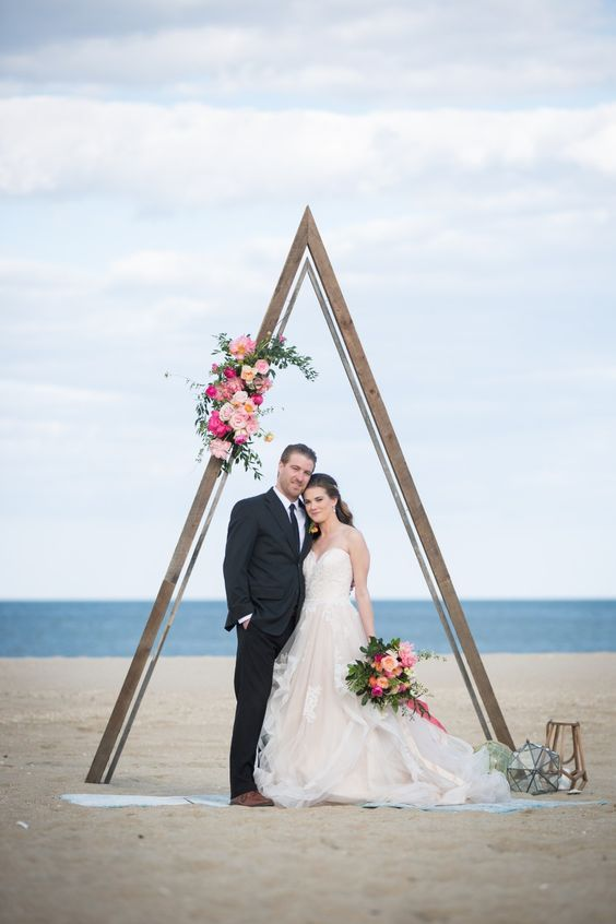 a romantic coastal wedding arch with bright blooms and greenery plus glass geometric candle lanterns