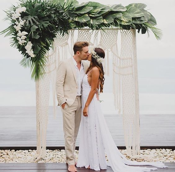 a boho tropical wedding arch with macrame, lush tropical greenery and white orchids