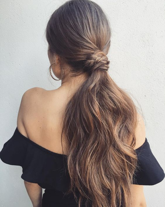a low ponytail with a sleek top, a twisted and braided part and much dimension on the ends