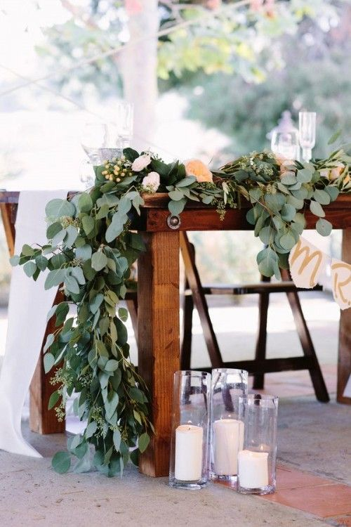 a lush eucalyptus table runner with some blush and peachy blooms is a gorgeous idea for summer
