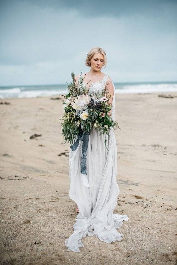 a moody coastal wedding bouquet with lush greenery reminding of the sea and a king protea