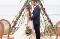 21 a teepee-styled wedding arch of birch branches, with greenery, fuchsia and burgundy blooms