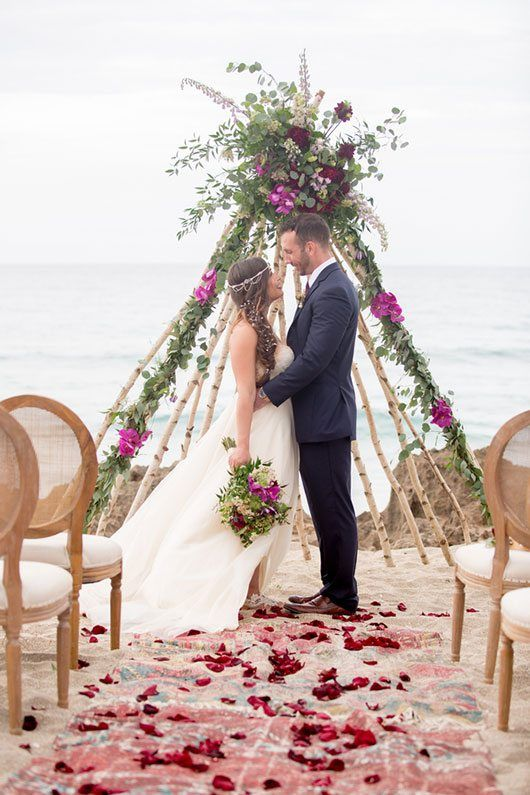 a teepee-styled wedding arch of birch branches, with greenery, fuchsia and burgundy blooms
