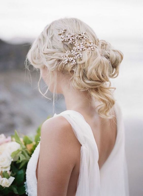 a wavy and messy updo with curls down and a sparkling rhinestone headpiece