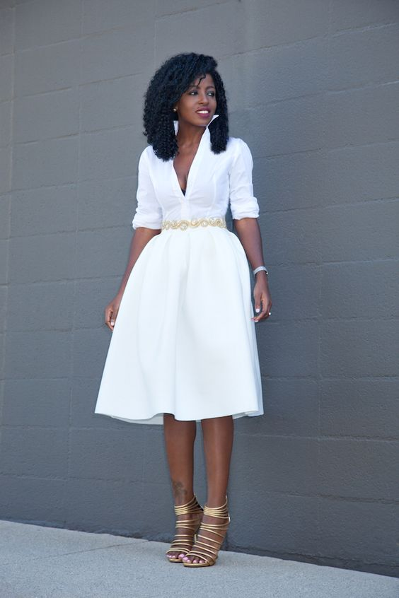 a white button down and a full pleated skirt, an embellished belt and metallic shoes