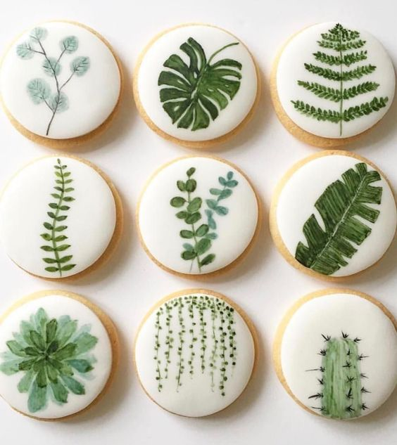 pretty glazed cookies with greenery of various kinds for a desert or botanical wedding