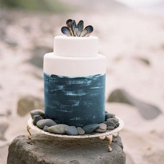 this brushstroke navy wedding cake with oyster shells looks rather nautical and coastal