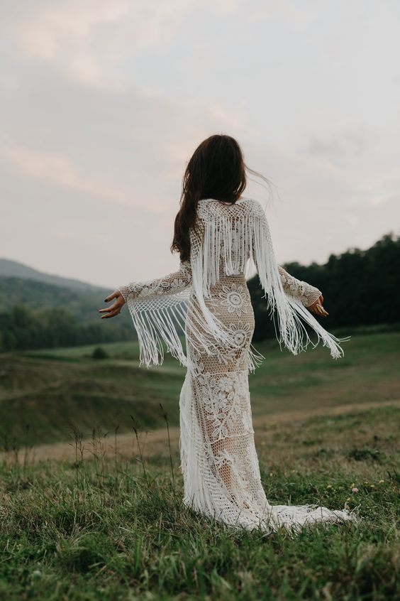 a boho lace sheath wedding dress with long fringed sleeves for a wild look