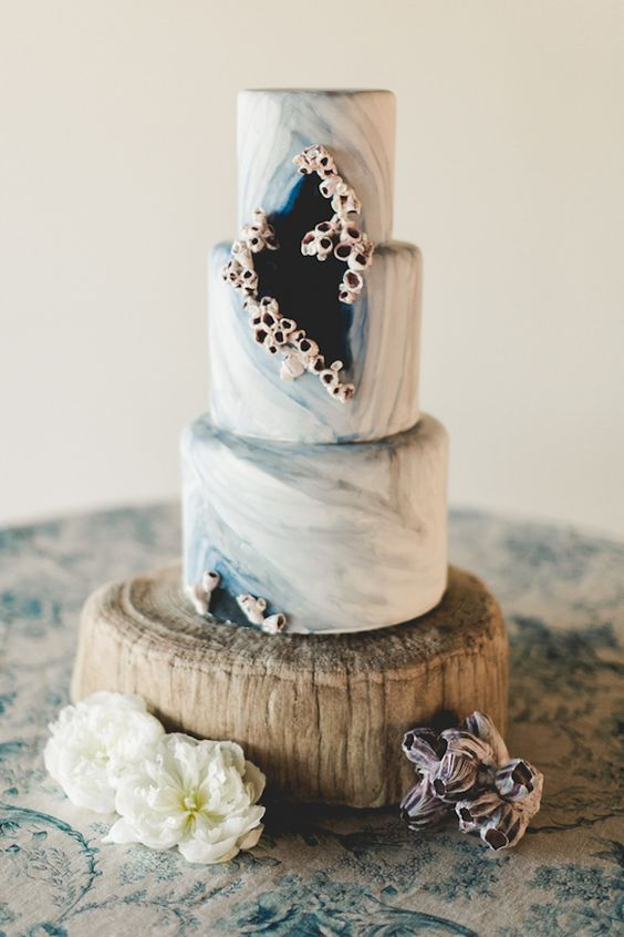 a fantastic marble grey wedding cake decorated with sugar sea creatures