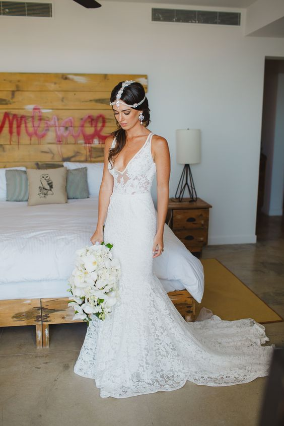 a lace mermaid wedding dress with a deep v-neckline, thick straps and a train plus a boho headpiece