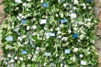22 a lush greenery and white blooms wall with escort cards is a chic and very creative idea to display them
