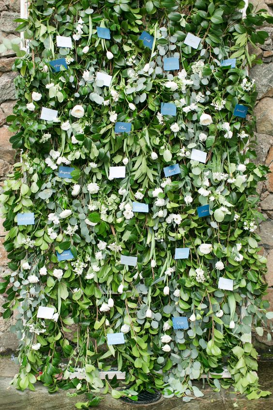 a lush greenery and white blooms wall with escort cards is a chic and very creative idea to display them