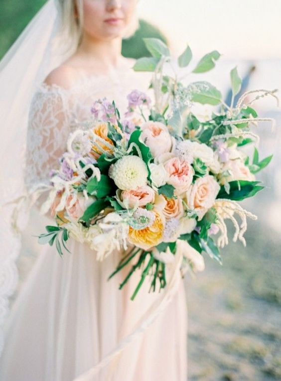 a lush oversized wedding bouquet in the shades of blush, muted yellow, mauve and cream plus greenery