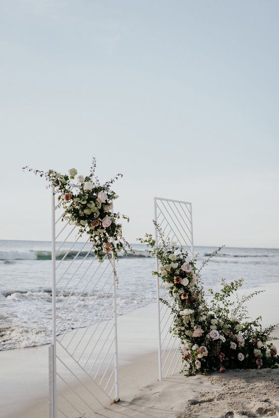 a modern geometric backdrop with lush florals and greenery for a unique beach wedding look