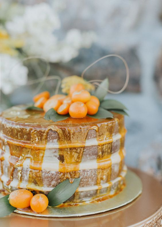 a naked wedding cake with honey drip and kumquats for a bold summer wedding