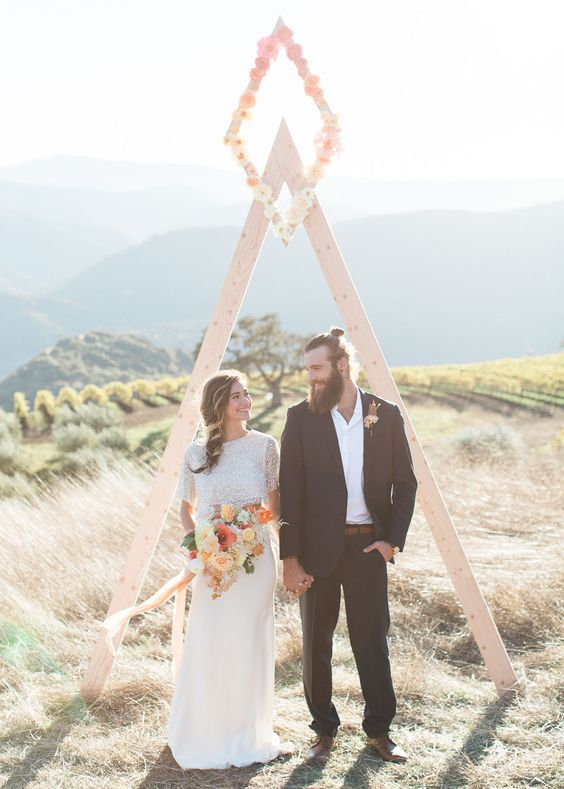 a simple triangle wooden arch with a rhomb on top fully covered with ombre blooms from pink to ivory