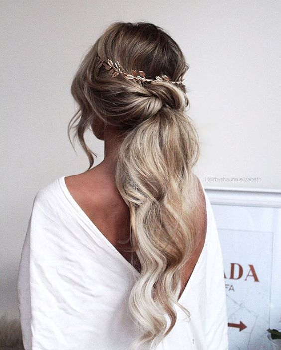 a low twisted textured ponytail with waves, locks down and a hair vine looks very romantic