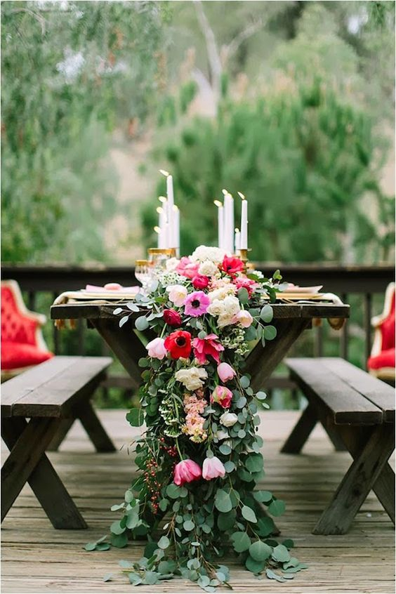 a lush greenery table runner with red, pink and blush flowers integrated looks colorful and chic