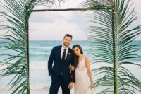 23 a modern tropical wedding arch done with two oversized tropical branches