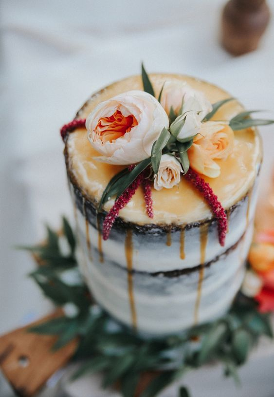 a semi naked wedding cake with honey drip, blush blooms and lisianthus on top
