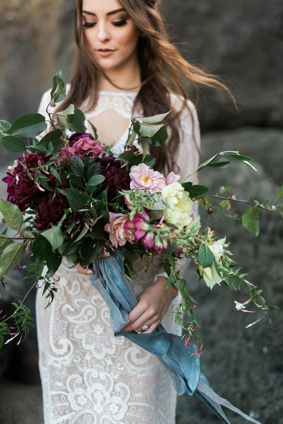 a textural wedding bouquet with greenery, blush, pink and burgundy blooms