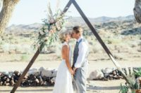 23 a triangle wooden arch with greenery and lush blush flowers on one side looks rather glam