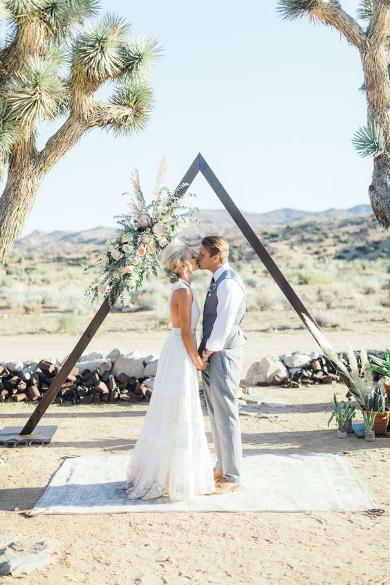 a triangle wooden arch with greenery and lush blush flowers on one side looks rather glam