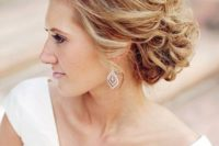 23 an airy and breezy wavy updo with curls and volume on top for an elegant feel