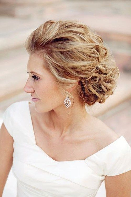 an airy and breezy wavy updo with curls and volume on top for an elegant feel